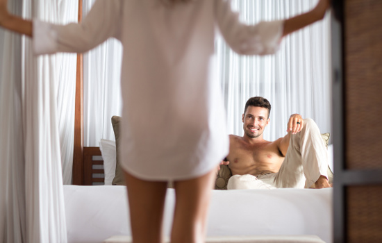 woman seduces her boyfriend in the bedroom, he lying on bed and looking at her